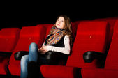 Young attractive woman sitting in a cinema — Stock Photo