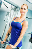 Young woman doing body-building in the Gym — Stock Photo