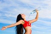 Fille de sport en rouge uniforme avec une bouteille d'eau — Photo