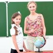 Teacher and the schoolgirl in the classroom — Stock Photo