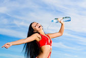 Sport girl in red uniform with a bottle of water — ストック写真