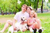 Happy young family with Labrador — Stock Photo