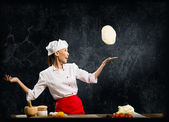 Asian female chef tosses a piece of dough — Stock Photo