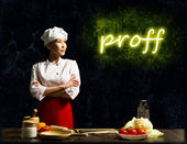 Asian female chef looking at the glowing proff — Stock Photo