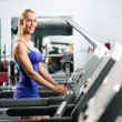 Attractive young woman runs on a treadmill — Stockfoto