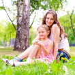Foto Stock: Mother and daughter sitting together on grass