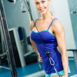 Stock Photo: Young womdoing body-building in Gym