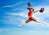 Joven animadora en traje rojo de salto — Foto de Stock