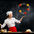 Asian woman chef juggling with vegetables — Stock Photo