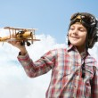 Boy in helmet pilot playing with a toy airplane - Stock Photo