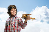 Boy in helmet pilot playing with a toy airplane — Stock Photo
