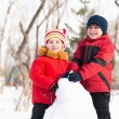 Boy and girl playing with snow in winter park - ストック写真