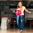 Pleasant young woman throws a bowling ball - Stock Photo