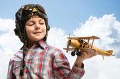 мальчик в шлем экспериментальных играть с игрушкой самолет — Стоковое фото