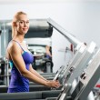 Attractive young woman runs on a treadmill — Stok fotoğraf