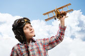 Boy in helmet pilot playing with a toy airplane — 图库照片