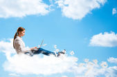Young girl running in the clouds with a laptop — Stock Photo