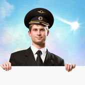 Pilot in the form of holding an empty billboard — Stock Photo