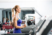 Attractive young woman runs on a treadmill — Stock Photo