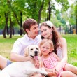 Stock Photo: Happy young family with Labrador