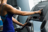 Woman adjusts the treadmill — Stock Photo