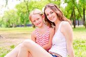 Mor och dotter sitter tillsammans på gräset — Stockfoto