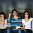 Group of young watching TV on the couch — Stock Photo #24865201
