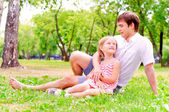 Father and daughter sitting together on the grass — Stock Photo