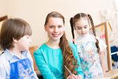 Crianças com o professor envolvido em pintura — Foto Stock