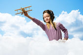 Girl in helmet pilot playing with a toy airplane — Foto de Stock
