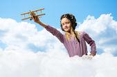 Flicka i hjälm pilot leker med en leksak flygplan — Stockfoto