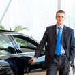 Dealer stands near a new car in the showroom — Stockfoto