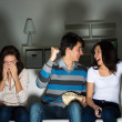 Group of young watching TV on the couch — Stock Photo