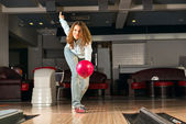 Pleasant young woman throws a bowling ball — Stockfoto