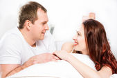Young man and woman lying together in bed — Stock Photo