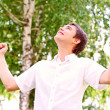 Young man looking to the sky, holding his hands up — Stock Photo