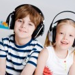 Brother and sister listening music with headphones — Stock Photo