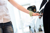 Woman opens the door to a new car — Stock Photo