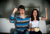 Couple watching TV on the couch — Stockfoto