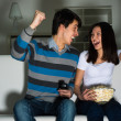 Couple watching TV on the couch — Stock Photo #26138779