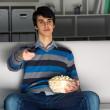 Young man watching television with popcorn — Stock Photo #26138793