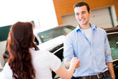 Man shaking hands with car salesman — Stock Photo