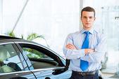 Satıcı yeni bir araba showroom yakın duruyor — Stok fotoğraf