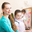 Children with the teacher engaged in painting — Stock Photo #26600985