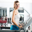 Attractive young womruns on treadmill — Stock Photo #26601247