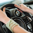 Woman's hands holding on to the wheel of a new car — Stock Photo