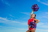 Young cheerleader in red costume with pampon — Stockfoto