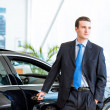 Dealer stands near a new car in the showroom — Stock Photo #27771985