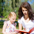 Stock Photo: Girl and young womreading book together