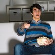 Young man watching television with popcorn — Stock Photo #27772223